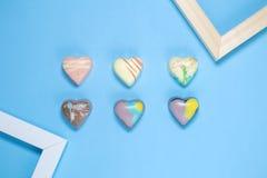 与框架的六比利时巧克力心脏在蓝色背景 库存照片