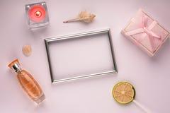 与框架的紫色背景的照片、礼物盒、蜡烛和香水,与空的空间 免版税图库摄影
