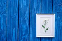 与框架的花卉现代设计在蓝色木桌面看法嘲笑 免版税库存照片