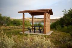 与桌和椅子的木被盖的野餐小屋 库存图片