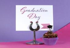 与桌地方的毕业典礼举行日桃红色和紫色党杯形蛋糕ho 库存图片