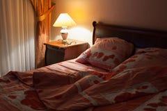 与桌灯的卧室内部在夜间 免版税图库摄影