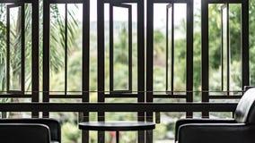 与桌的Nterior设计和椅子现出轮廓森林视图 免版税库存图片