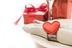 与桌餐位餐具的情人节晚餐与红色礼物,与银器的心脏在白色背景 关闭 华伦泰` s加州 免版税图库摄影