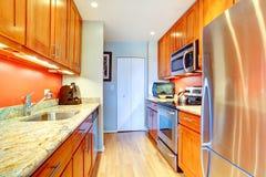 与桔子后面飞溅和花岗岩上面的狭窄的厨房内部 库存图片