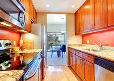 与桔子后面飞溅和花岗岩上面的狭窄的厨房内部 库存照片