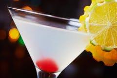与桔子和一棵樱桃片断的装饰的明亮的可口鸡尾酒在玻璃的底部在桌上在restaura 图库摄影