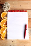 与桔子和蕃茄切片的日志书在木背景 免版税库存照片