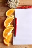 与桔子和蕃茄切片的日志书在木背景 免版税图库摄影