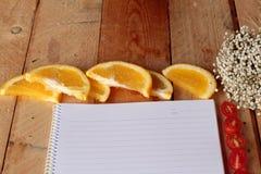 与桔子和蕃茄切片的日志书在木背景 库存图片