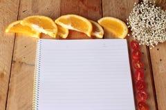 与桔子和蕃茄切片的日志书在木背景 图库摄影