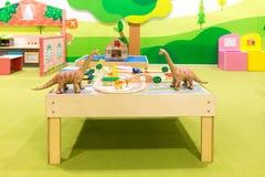 与桥梁、议院、树和玩具恐龙的铁路结构 免版税库存照片