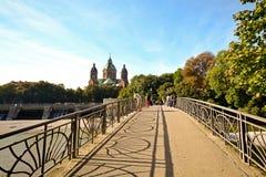 与桥梁的河沿横跨伊萨尔河河在慕尼黑,巴伐利亚德国 免版税库存照片