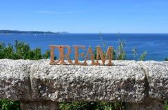 与梦想木标志的海岸在扶手栏杆和树 蓝色海,好日子 Rias拜克萨,西班牙 免版税库存图片