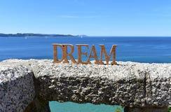 与梦想木标志的海岸在扶手栏杆 蓝色海,好日子 Rias拜克萨,西班牙 图库摄影
