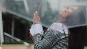 与检查是否的伞的愉快的年轻女商人跳舞雨中止 微笑和享受雨的末端她 股票录像