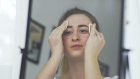 与棉花棒的妇女清洗的面孔在镜子前面 影视素材