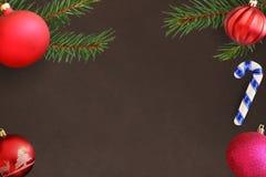 与棍子,桃红色和红色波浪愚钝的球的圣诞树分支在黑暗的背景 库存照片