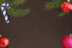 与棍子,桃红色和红色波浪球的圣诞树分支在黑暗的背景 库存图片
