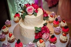 与棒棒糖、松饼、蛋糕和甜点的甜婚宴喜饼在婚礼聚会区域  广告风景的概念  免版税库存图片
