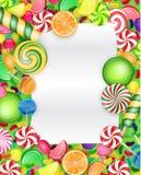 与棒棒糖和橙色切片的五颜六色的糖果背景 免版税库存图片