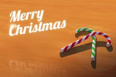 与棒棒糖的圣诞快乐在木表贺卡 库存照片