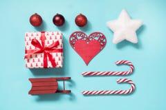 与棒棒糖的圣诞节汇集,心脏,球,嘲笑的红色sleid在蓝色的模板设计 平的位置 顶视图 库存照片