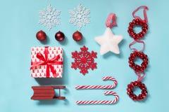 与棒棒糖的圣诞节汇集,心脏,球,嘲笑的红色sleid在蓝色的模板设计 平的位置 顶视图 免版税库存照片