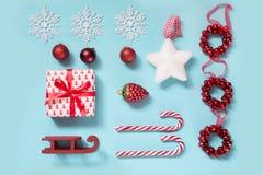 与棒棒糖的圣诞节汇集,心脏,球,嘲笑的红色sleid在蓝色的模板设计 平的位置 顶视图 免版税图库摄影