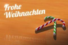 与棒棒糖的Frohe Weihnachten在木表贺卡 免版税图库摄影