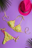 与棕榈叶的夏天背景、桃红色时尚帽子和比基尼泳装在紫罗兰色或紫色背景,旅行和假期概念,上面 免版税库存照片