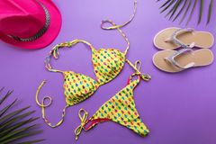 与棕榈叶的夏天背景、桃红色时尚帽子和比基尼泳装在紫罗兰色或紫色背景,旅行和假期概念,上面 免版税库存图片