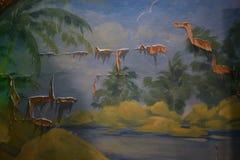 与棕榈树、地球和天空的被绘的风景在老墙壁上 免版税库存图片