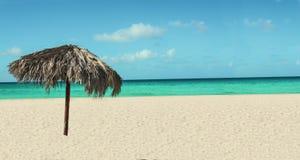 与棕榈树伞,天蓝色的海洋的异乎寻常的海滩 免版税库存图片