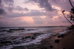 与棕榈树剪影和印度洋波浪的热带日落 太阳、天空、海、波浪和沙子 图库摄影