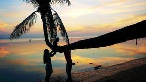 与棕榈树剪影的热带日落在海洋海滩,幸福家庭戏剧剪影与女儿的棕榈树的 股票视频