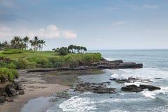 与棕榈树和一个豪华的绿色海岛的碎波 免版税库存照片