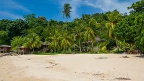 与棕榈树和小屋的田园诗海滩 免版税库存照片