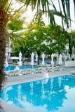 与棕榈树的游泳池,在日落时间的白色伞 免版税库存照片