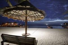 与棕榈树的热带沙滩和在日落的竹子小屋 库存图片