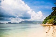 与棕榈树的热带海滩和在距离的帆船 库存图片
