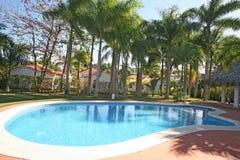 与棕榈&用餐眺望台的游泳池周围 免版税库存图片