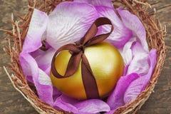 与棕色丝带的复活节金黄鸡蛋在嵌套。 免版税图库摄影