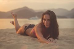 与棕色享受暑假的头发佩带的比基尼泳装的有吸引力的模型说谎在沙滩在日落海和 库存照片
