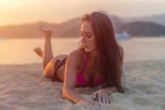 与棕色享受暑假的头发佩带的比基尼泳装的有吸引力的模型说谎在沙滩在日落海和 免版税库存图片