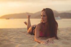 与棕色享受暑假的头发佩带的比基尼泳装的有吸引力的模型说谎在沙滩在日落海和 图库摄影