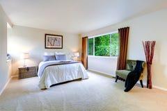 与棕色帷幕的明亮的主卧室内部 免版税库存照片