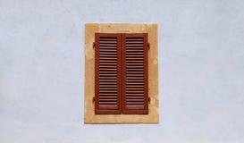 与棕色快门的闭合的窗口在蓝色古老墙壁上 免版税图库摄影