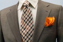 与棕色方格的关系和橙色handker的夹克 库存图片