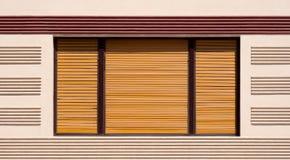 与棕色木快门的闭合的窗口 免版税库存照片